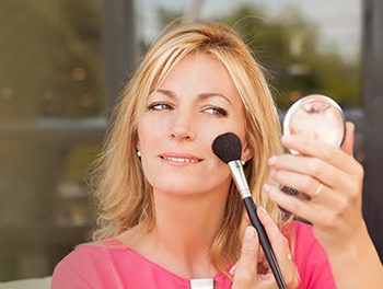 Beautiful woman doing her makeup before a date