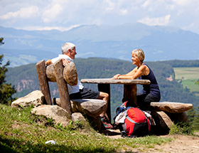 Older couple having a picnic at a table during a mountain hike